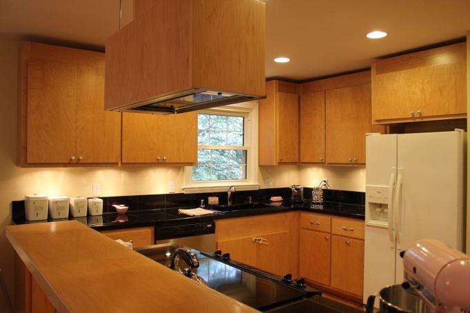 kitchen light wood black counters built in wood range hood