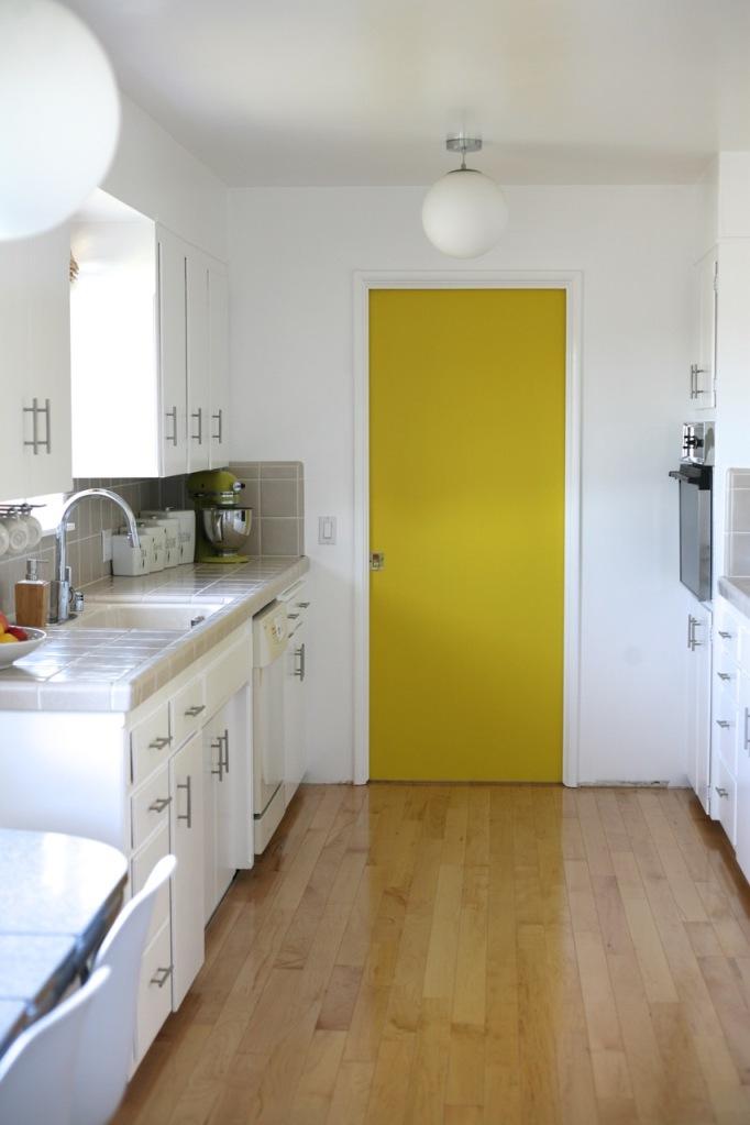 yellow pocket door kitchen mid century white cabinets wood floor behr ultra bright white paint