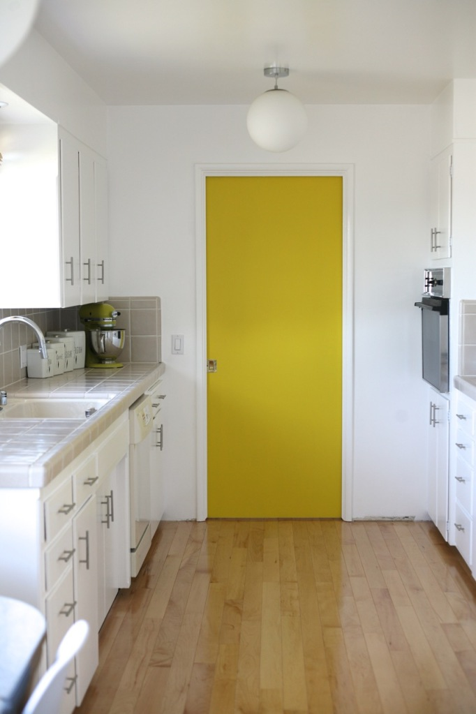 yellow pocket door kitchen mid century white cabinets wood floor