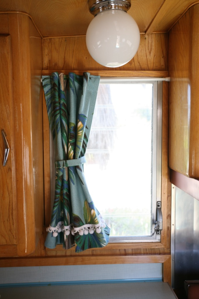 Shasta trailer vintage interior kitchen window bark cloth curtains globe light turquoise counters