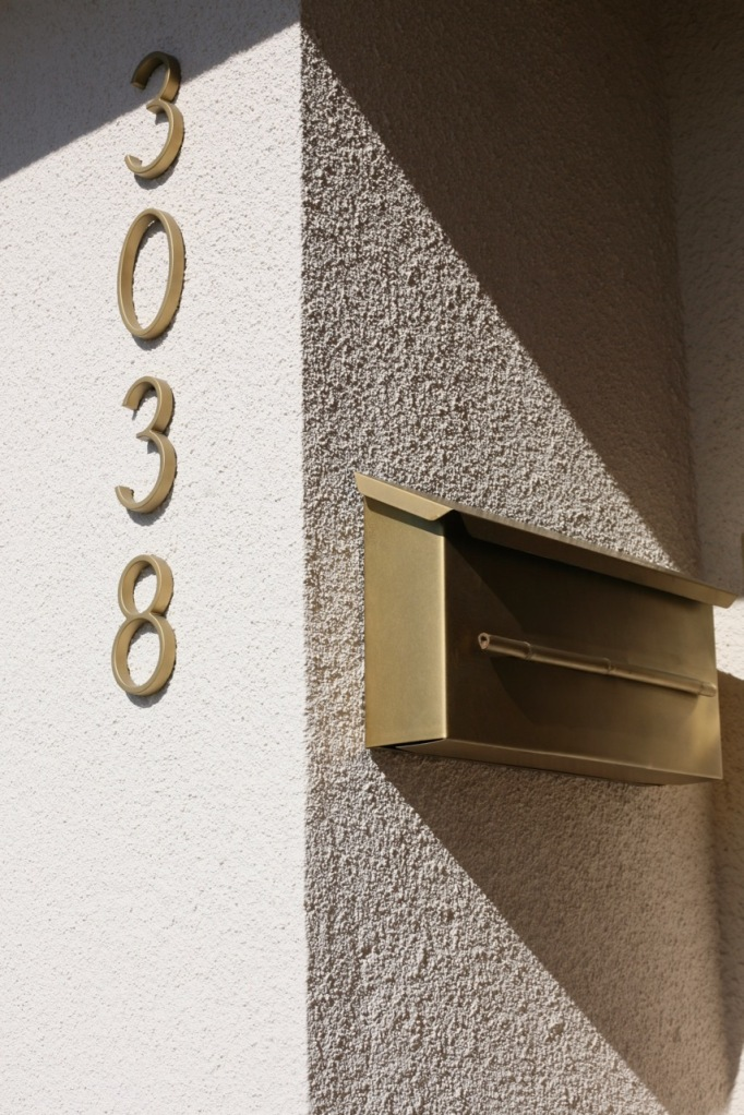 mid century house address numbers mailbox neutra brass gold porch stucco front door