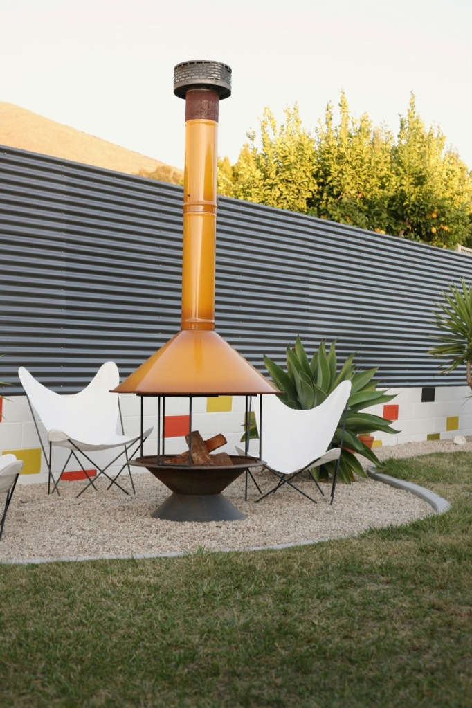 mid century backyard with vintage butterfly chairs fireplace and corrugated fence
